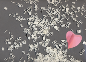 jumble of cut out letters and a heart